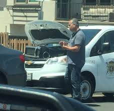 a man heating up his lunch using a microwave connected to his car battery