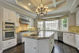 the kitchen features a large center island with marble countertop along with a chandelier light