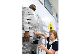 Students donate money to duct tape Belle Terre Elementary Principal Culver  to a wall - Second-grader Isabella Blair adds a piece of tape to Principal  Culver. Photo by Paige Wilson | Palm