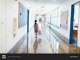 hallway at school. young girl walking down a school hallway at