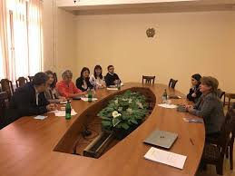 six diity rights advocates sit at a large round conference table from two parliamentarians