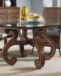 dining room curving brown wooden legs with round glass top feat brown rattan chairs placed