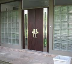 elegant brown mahogany wood panels modern front door with double chrome pull handles and two side