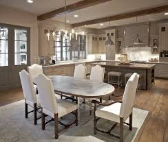 kitchen with coffee stained wood box beams gray french doors oval top lucite base dining table white and camelback dining chairs with nailhead trim