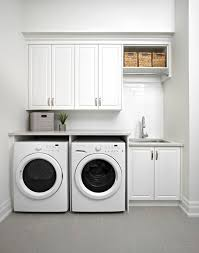 all white laundry room subway tile backsplash white cabinets large sink wicker