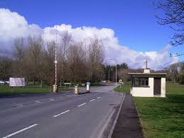 hospital gate lodge and entrance way with bus stop and access barrier in park setting