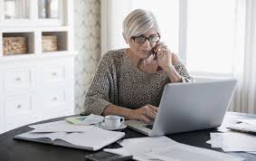 woman on laptop calling to get a homeowners insurance quote