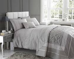 designer bed linen with white upholstered headboard and modern