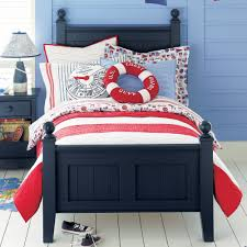 bedroom black wooden bed with red white striped bedding set connected by blue table lamp