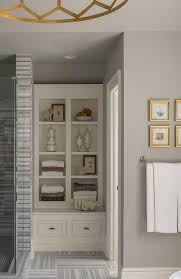 Gray and gold bathroom features a nook filled with built in shelves next to  a seamless glass shower clad in gray striped marble.