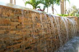 spillway for an infinity edge pool featuring a stacked stone wall laid over a waterproofing membrane