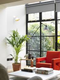 double roller shades are used to cover a wall of windows during the day