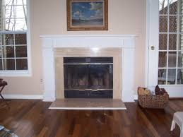 Interior. white fireplace mantel with beige around connected by beige wall  and brown wooden floor