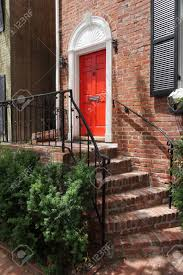 facade of houses stairs windows with black shutters red door green bushes