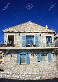 House With Stone Facing Blue Shutters And Elegant Balcony Near