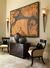 warm colour palette and dark espresso furnishings and decor with 2 torch wall sconces flanking a african inspired furniture
