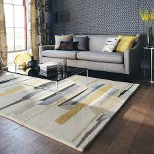 a saffron and grey printed living room rug next to a grey sofa with accented coloured
