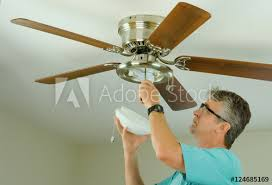 professional or diy do it yourself home owner doing ceiling fan repair work with the glass cover removed as he adjusts the fixture