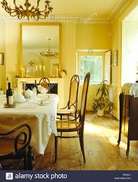 Yellow dining room chairs Prepare Antique Bentwood Chairs At Table Set For Lunch In Yellow Dining Room With Large Mirror Above Fireplace And Wooden Flooring Alamy Antique Bentwood Chairs At Table Set For Lunch In Yellow Dining Room