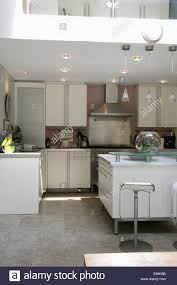Recessed Lighting In Modern White Kitchen With Grey Granite Flooring
