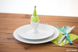 easter holidays tradition and object concept green colored egg in cup holder plates and cutlery on table at home stock photo and royalty free images