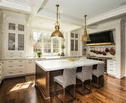 gold industrial pendants with brown kitchen island