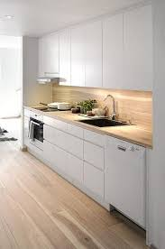 08 a minimalist white kitchen with sleek cabinets and a light colored wood countertop and backsplash plus a glass screen