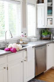 white farmhouse style kitchen with beautiful pink peonies in the sink