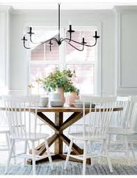 bria hammel interiors white windsor chairs sit on a black and white rug and surround a round stained trestle dining table lit by an iron chandelier in a
