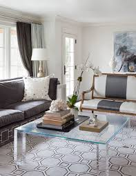 chic living room with white and gray striped settee square acrylic coffee table windows covered in blue and gray curtains frame charcoal gray velvet sofa
