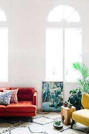 Red couch, white rug, pops of color in a white room