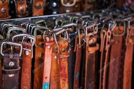 hand crafted leather belts with unique buckles on market in mexico stock photo