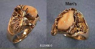 an elk s head and antlers hold the ivory in this unique ring gold nuggets are inlaid on the opposite side