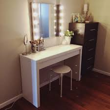 diy wooden makeup vanity table painted with white color and wall mounted rectangle lighted mirror with stool and brown cabinet with drawer in the corner