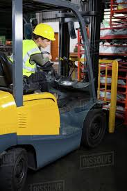 Confident Female Worker Driving Forklift In Factory Stock Photo