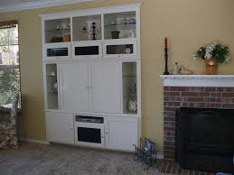 built in white entertainment center with glass shelves