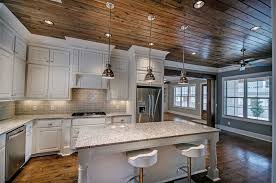 Rustic kitchen with white cabinets, snowfall granite counter and breakfast  bar island with chrome pendant