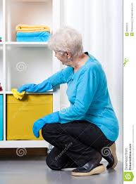 dusting furniture. Elderly Woman During Dusting Furniture