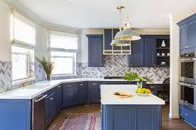 blue and white kitchen boasts red and blue runner placed in front of blue shaker cabinets accented with brass square knobs and topped with a white quartz