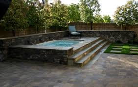 a prefab raised pool with steps and a stone finish instead of the traditional wood deck image legacy builders
