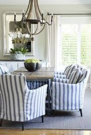 coastal dining room with reclaimed wood chandelier and blue and white striped slipcovered dining chairs via roses and rust by hercio dias