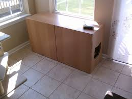 long and big wooden cat litter box with cat hole in room with tile near windows
