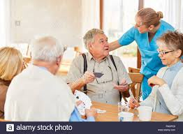 Geriatric Nursing Senior Group In Retirement Home While Playing Cards Together