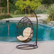 outdoor egg chair hanging on wooden platform near the pool
