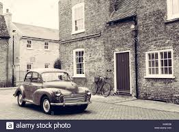 retro scene with vine british car 1950 style parked in front of victorian english building with red door black and white