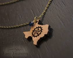 a necklace for texas steampunks the pendant is laser cut from cherry wood engraved with the lone star gear and has a small dark blue swarovski elements