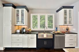 white cabinets with black crown molding and frosted glass doors frame kitchen window