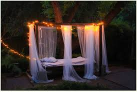 hanging bed with mosquito netting and string lights outoors