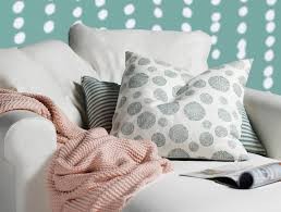 a green and white patterned cushion and pink throw new cushion cover