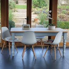 beautiful painted farmhouse table with contemporary eames style chairs create a beautiful look that is clic yet contemporary in any setting